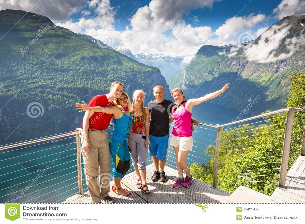 Happy friends relax on Geiranger fjord. People enjoy good weather in Norway.