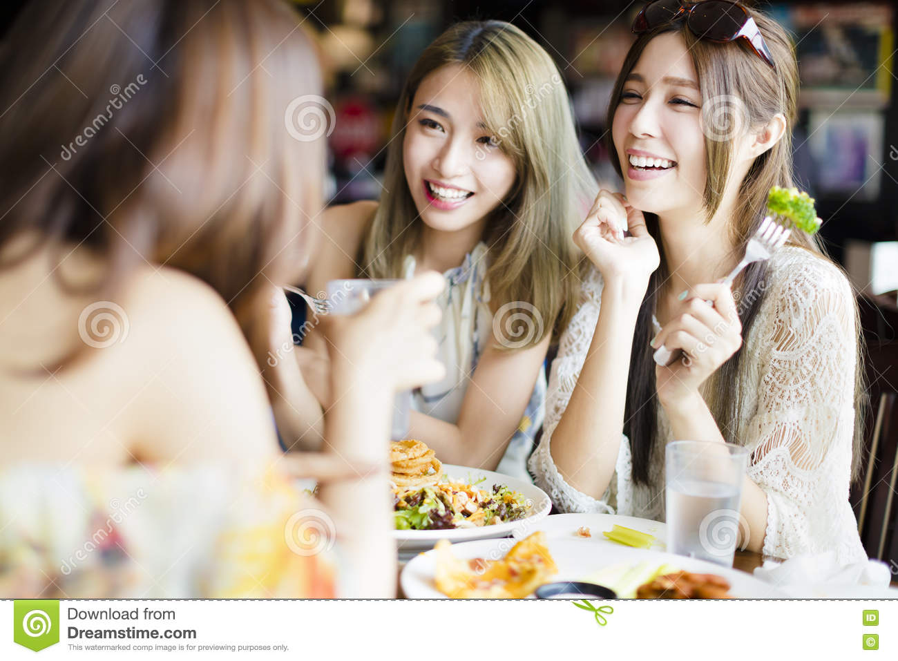 Happy friends sitting and chatting in restaurant