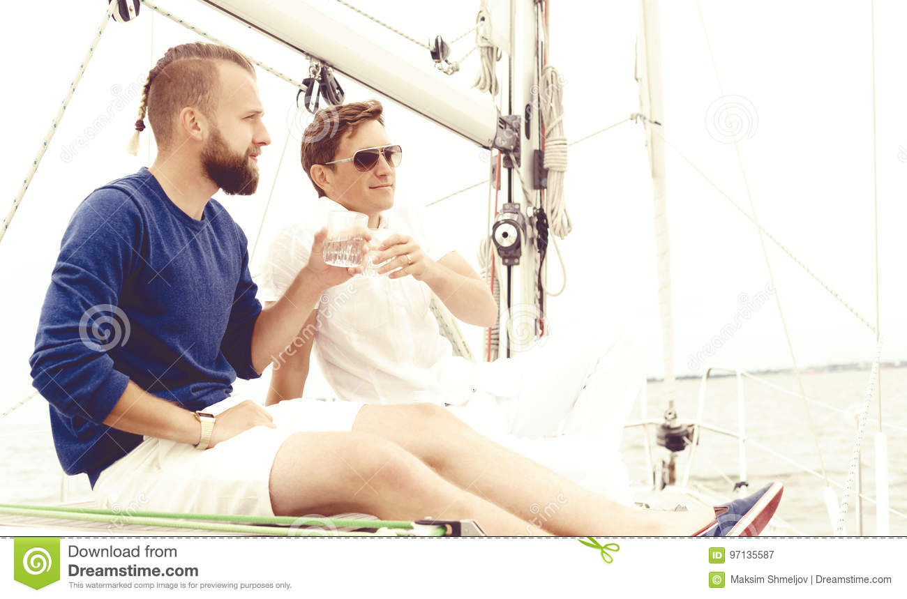 e1c00b84c3e Happy friends sitting together on a deck of a yacht enjoying a good day and  having a drink. Summer