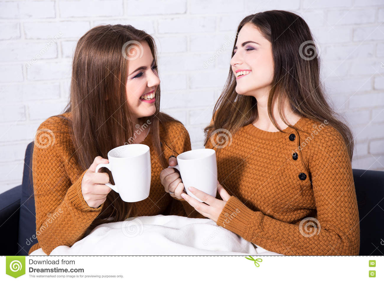 Happy friends talking and drinking coffee or tea