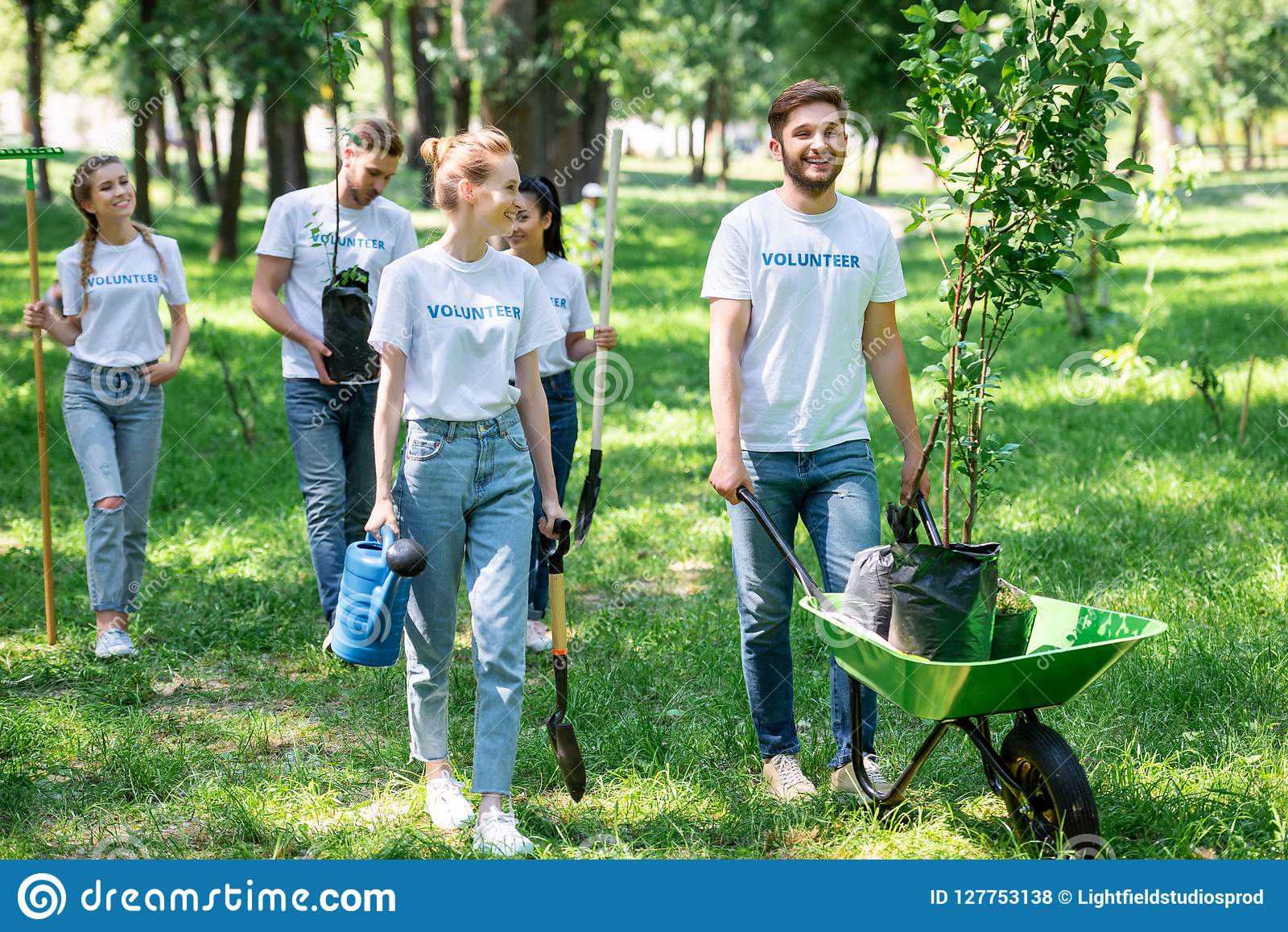 happy friends volunteering and planting trees