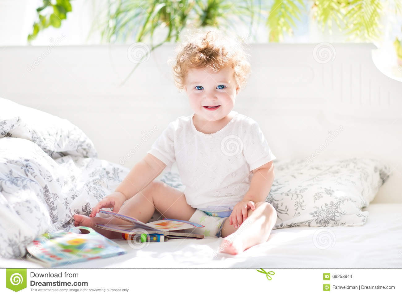 Baby Bed For Parents Bed - Happy funny baby reading a book in her parents bed stock photo
