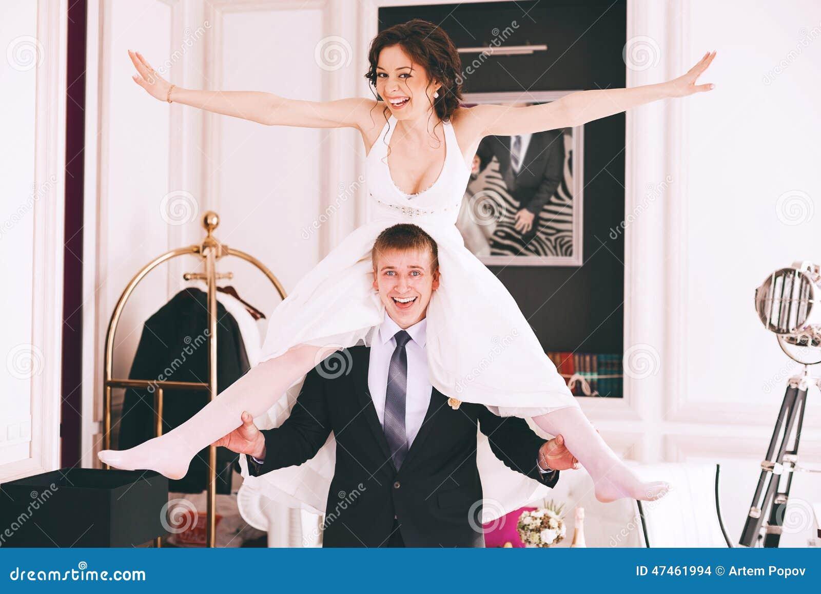 Happy Funny Bride Sitting On Groom Shoulders Stock Photo