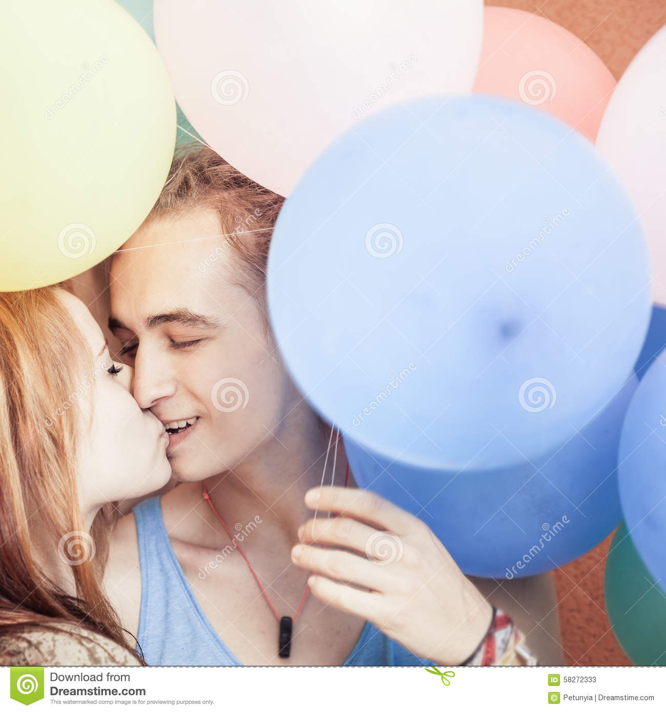 Happy and funny couple kissing at background of color balloons