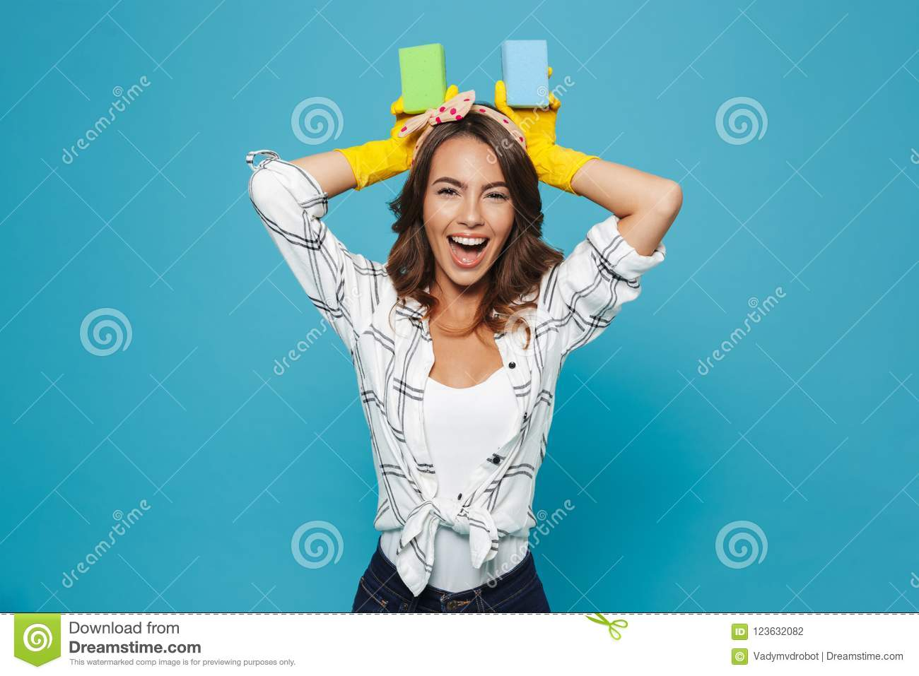 Happy funny housewife 20s in yellow rubber gloves for hands protection playing around and holding two sponges during cleaning, is