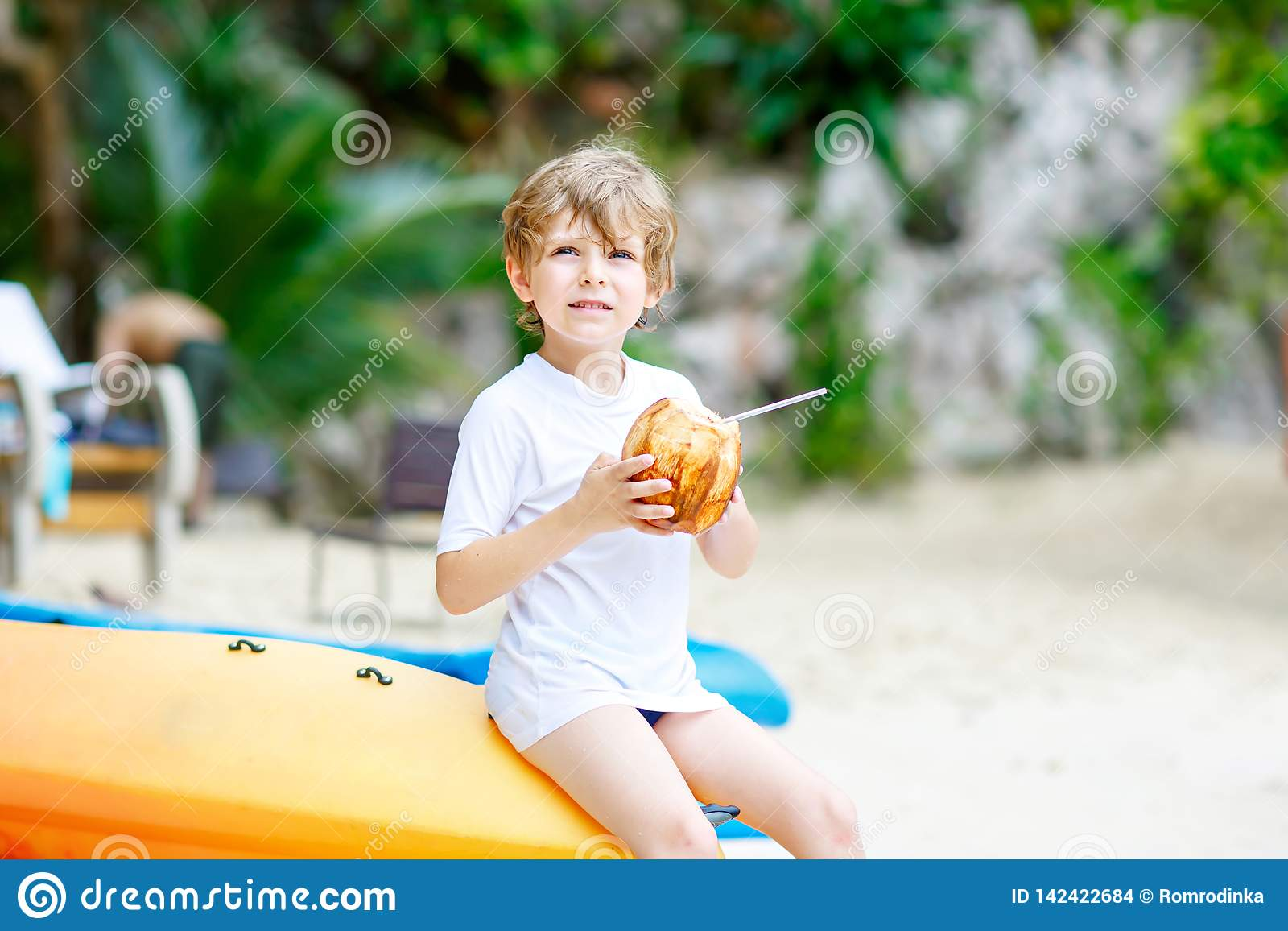 Happy funny little preschool kid boy drinking coconut juice on ocean beach. child playing on family vacations on