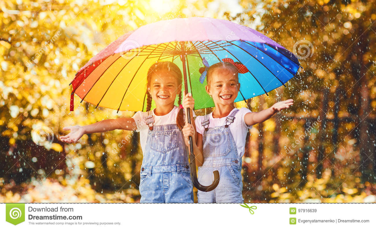 Happy funny sisters twins child girl with umbrella in autumn