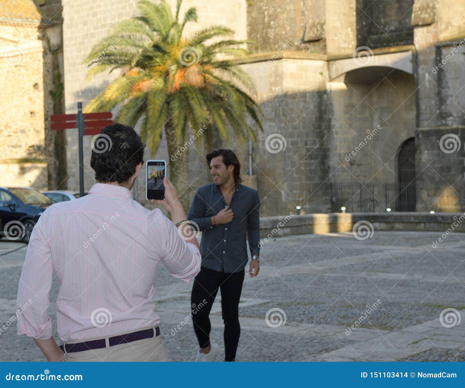 Happy gay couple taking photos