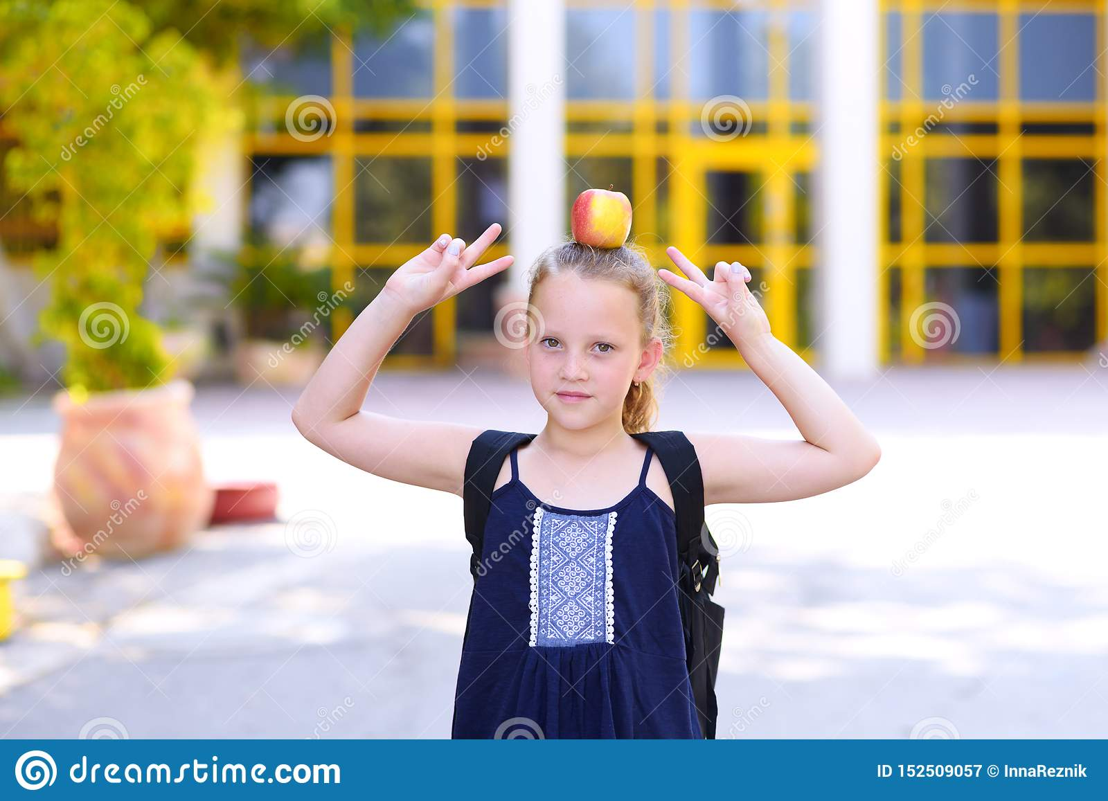 Little Girl Standing With Apple On Her Head  Stock Image