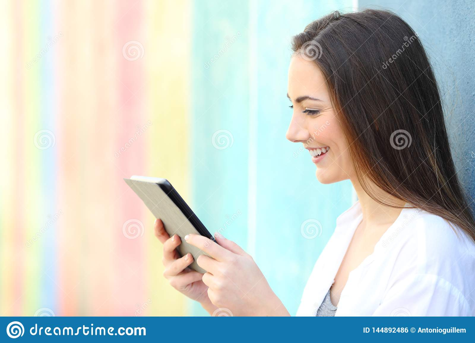 Happy girl on a colorful wall watching media on tablet