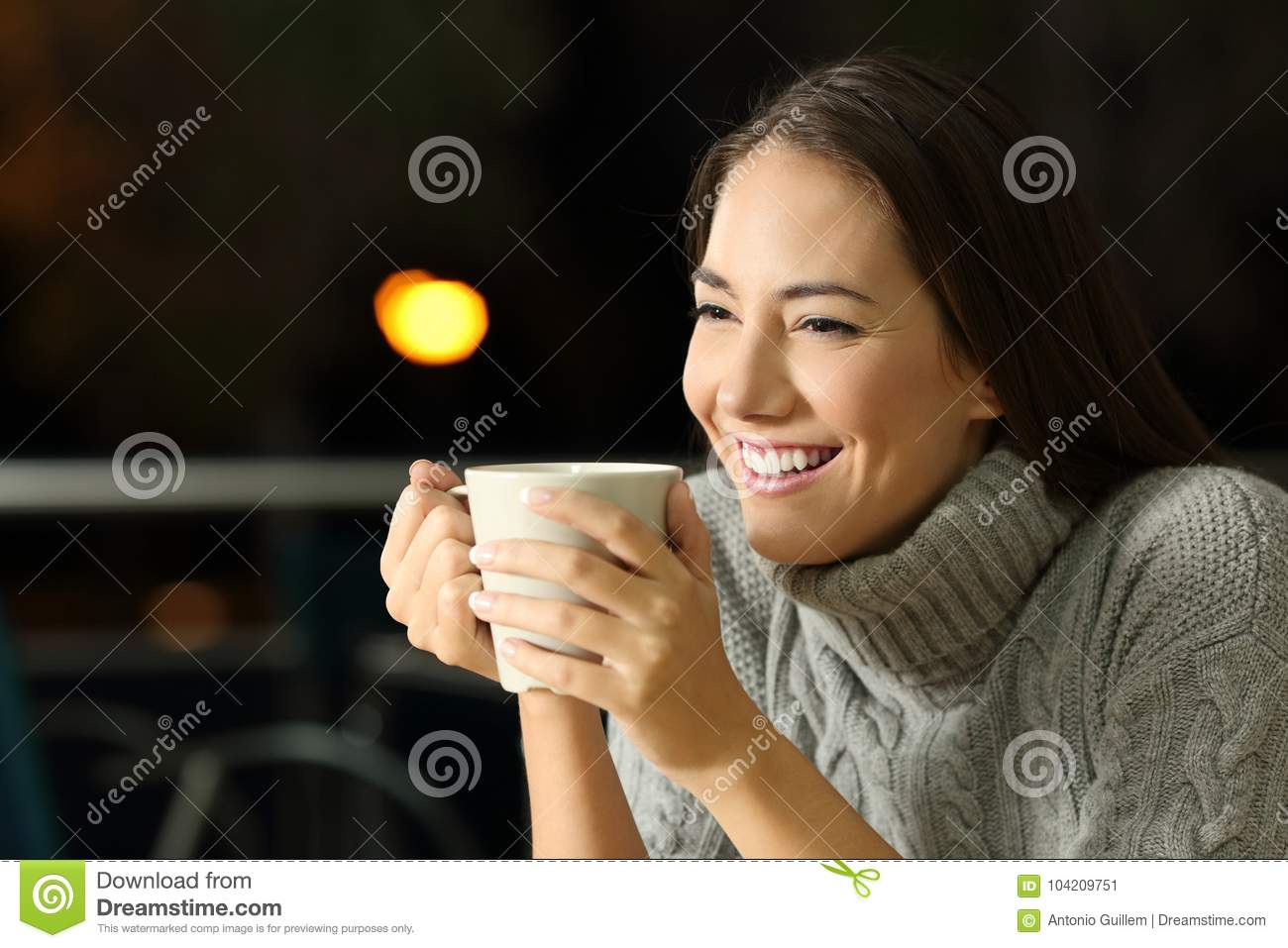 Happy girl drinking coffe in the night