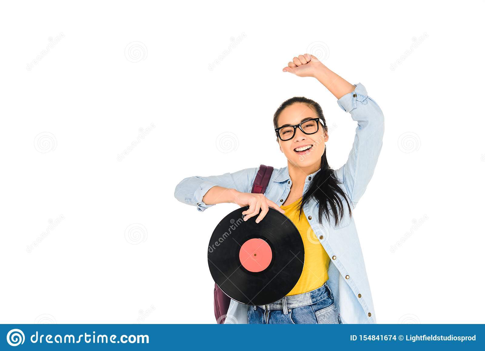 happy girl in glasses holding vinyl record with hand above head isolated