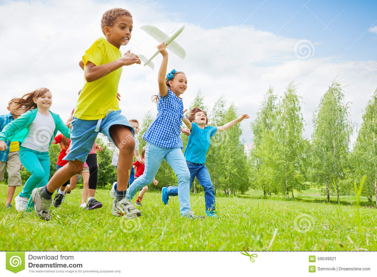 Happy girl holding airplane toy and children near