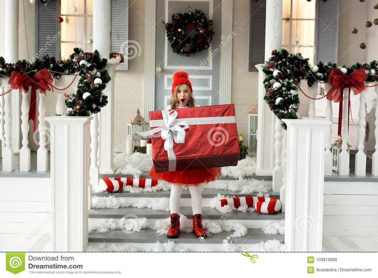 Happy girl holding a big box with a gift. christmas and people concept.