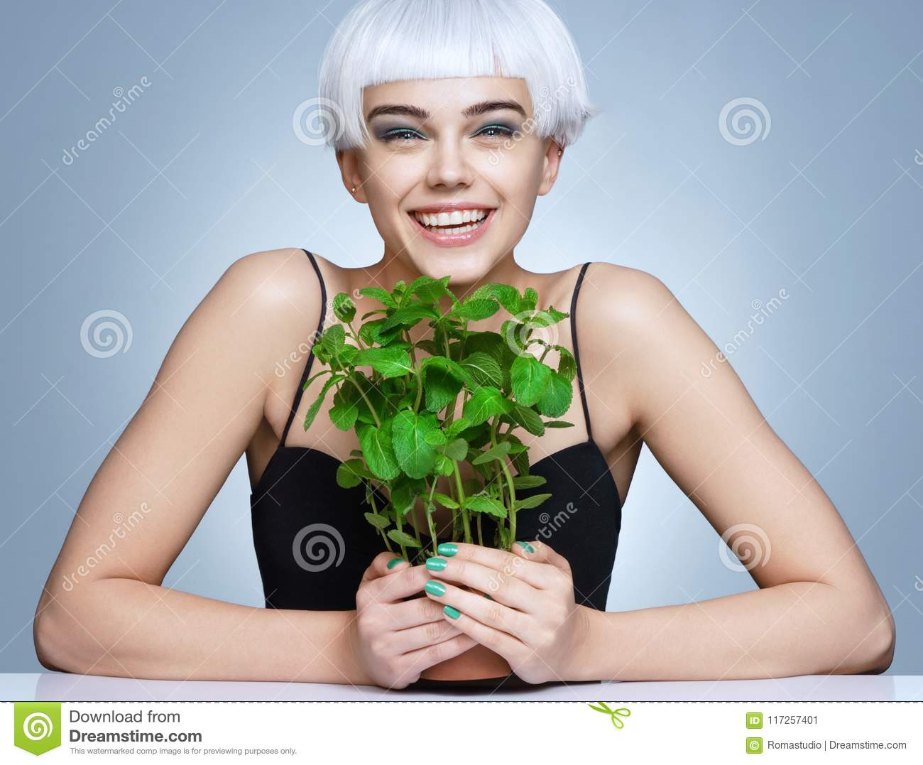 Happy girl holding pot of organic mint on blue background
