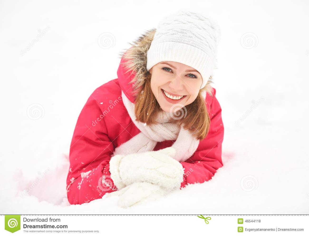 Happy girl laughs while lying on the snow in winter outdoors