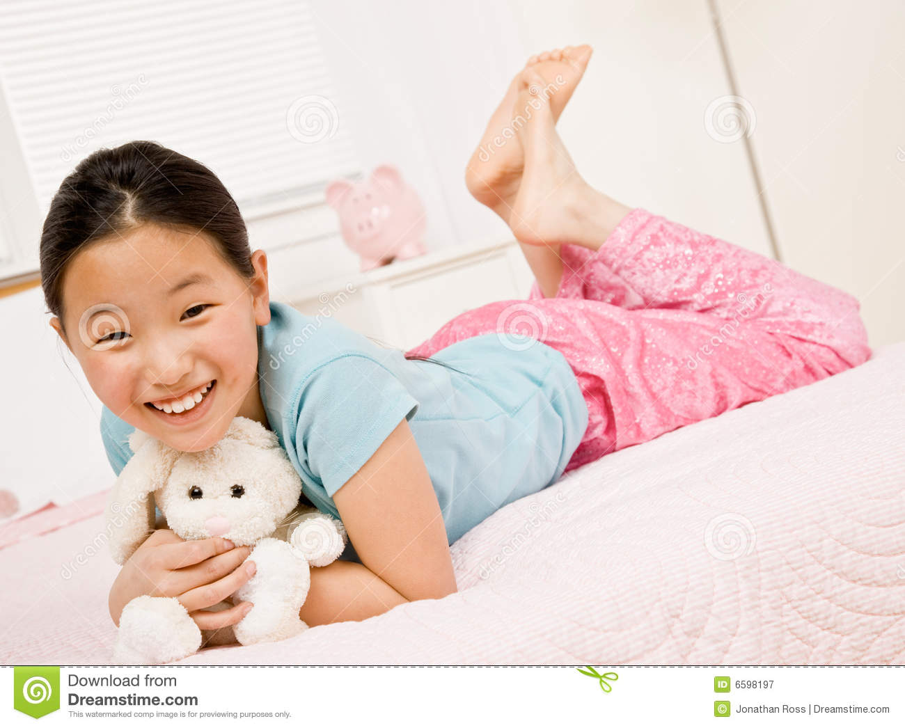 happy girl laying on bed with stuffed animal stock image image of lifestyles lifestyle 6598197. Black Bedroom Furniture Sets. Home Design Ideas