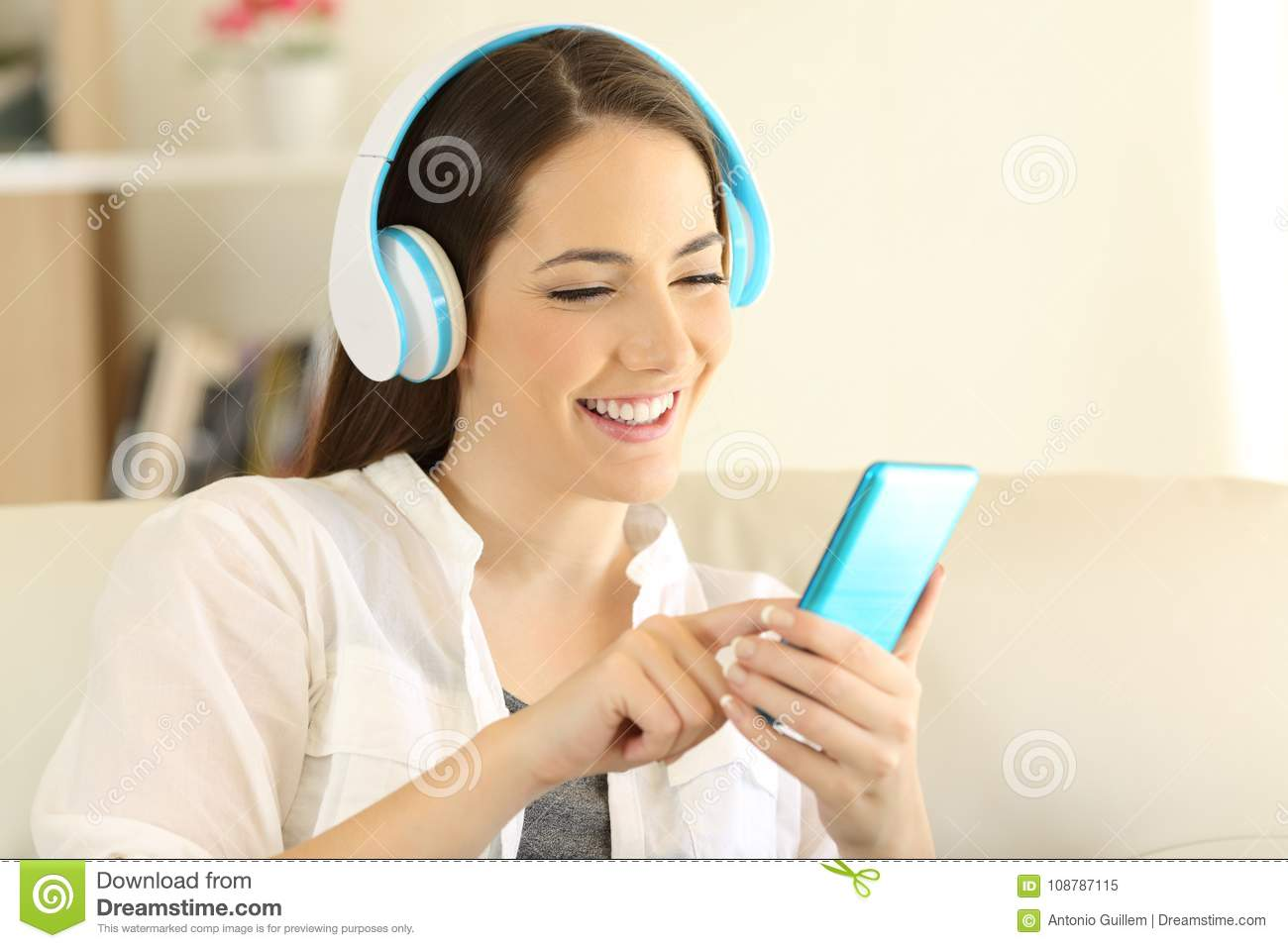 Happy Girl Listening To Music And Choosing Song In A Phone Stock