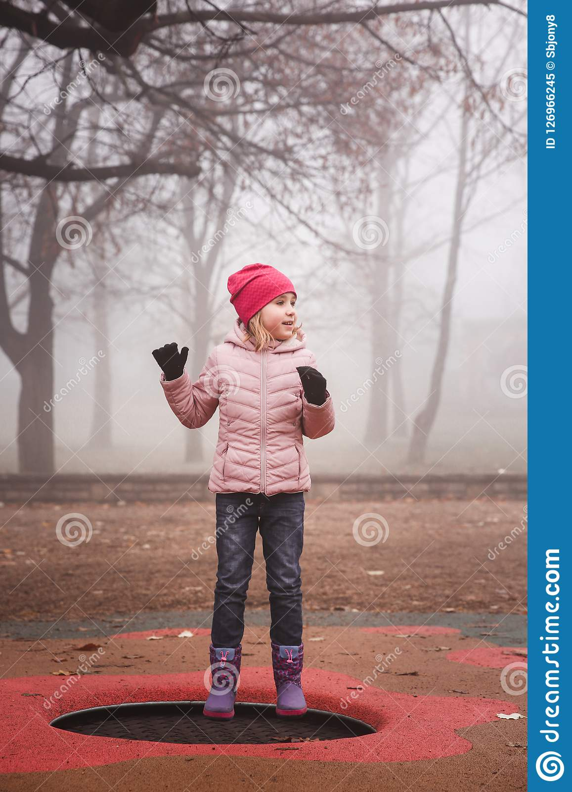 Happy girl in a pink jacket jumping on the trampoline outdoors in park. Autumn, misty forest.