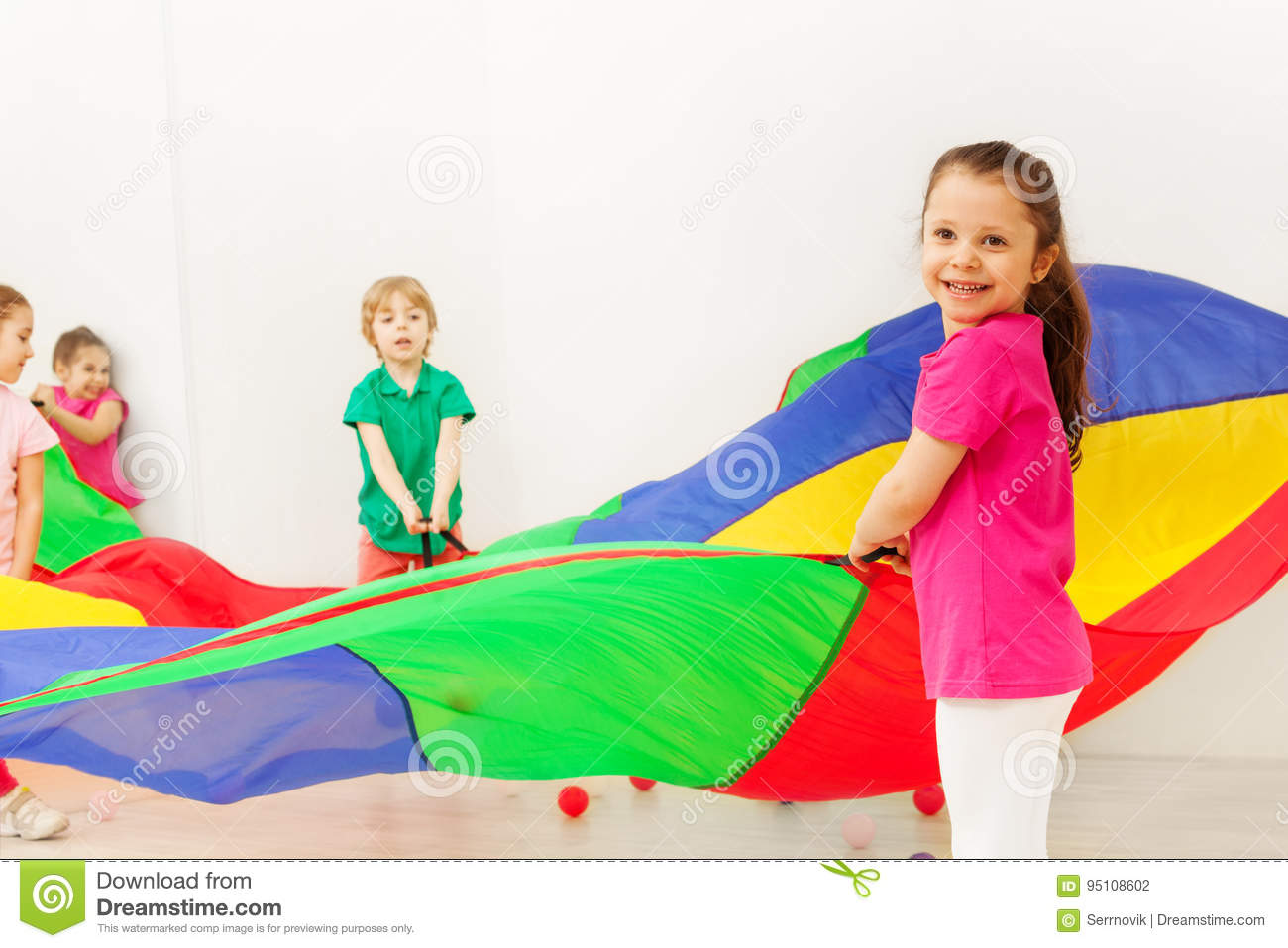 Happy girl playing with colorful parachute in gym
