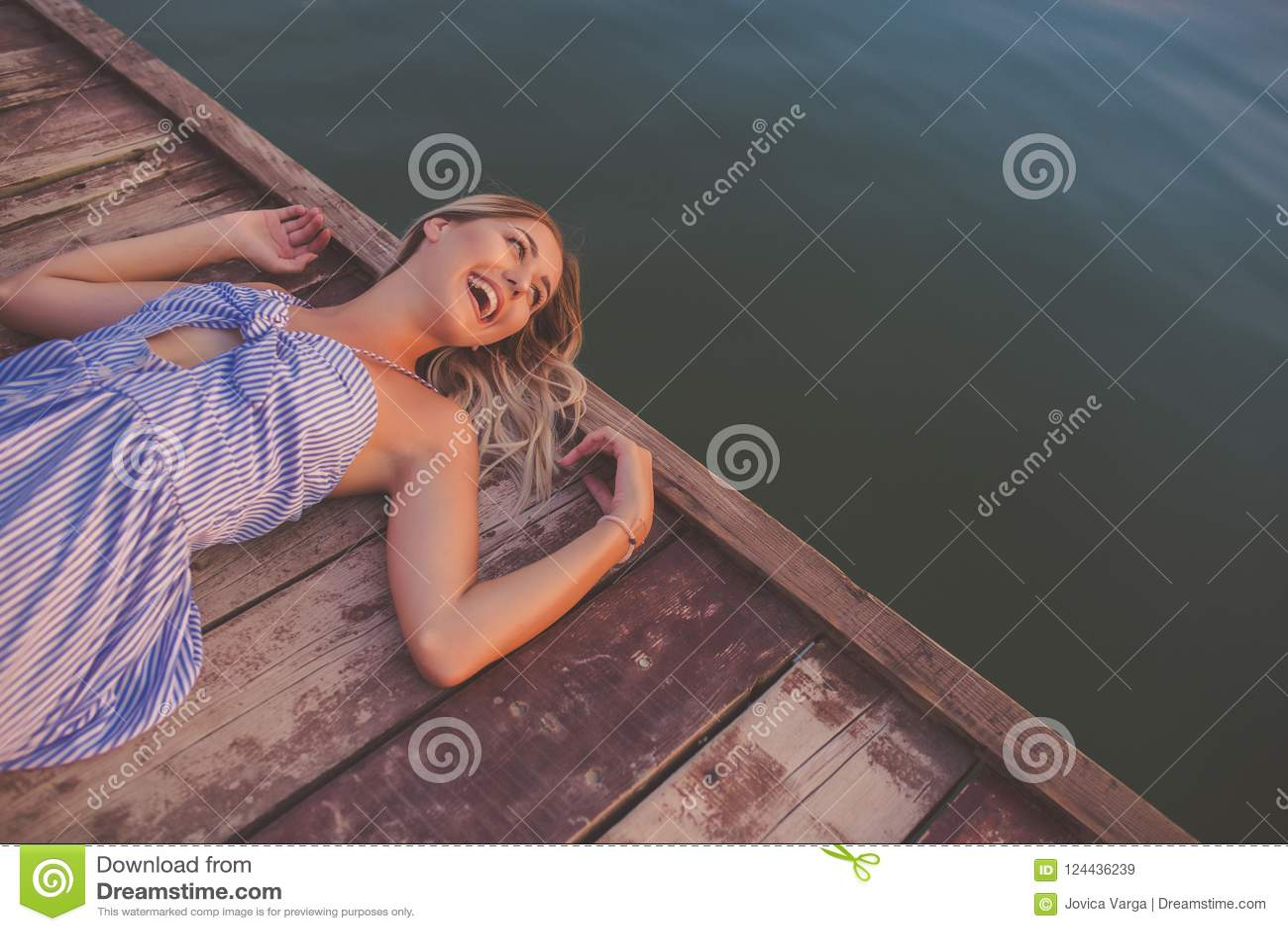 Happy girl posing on wooden pier