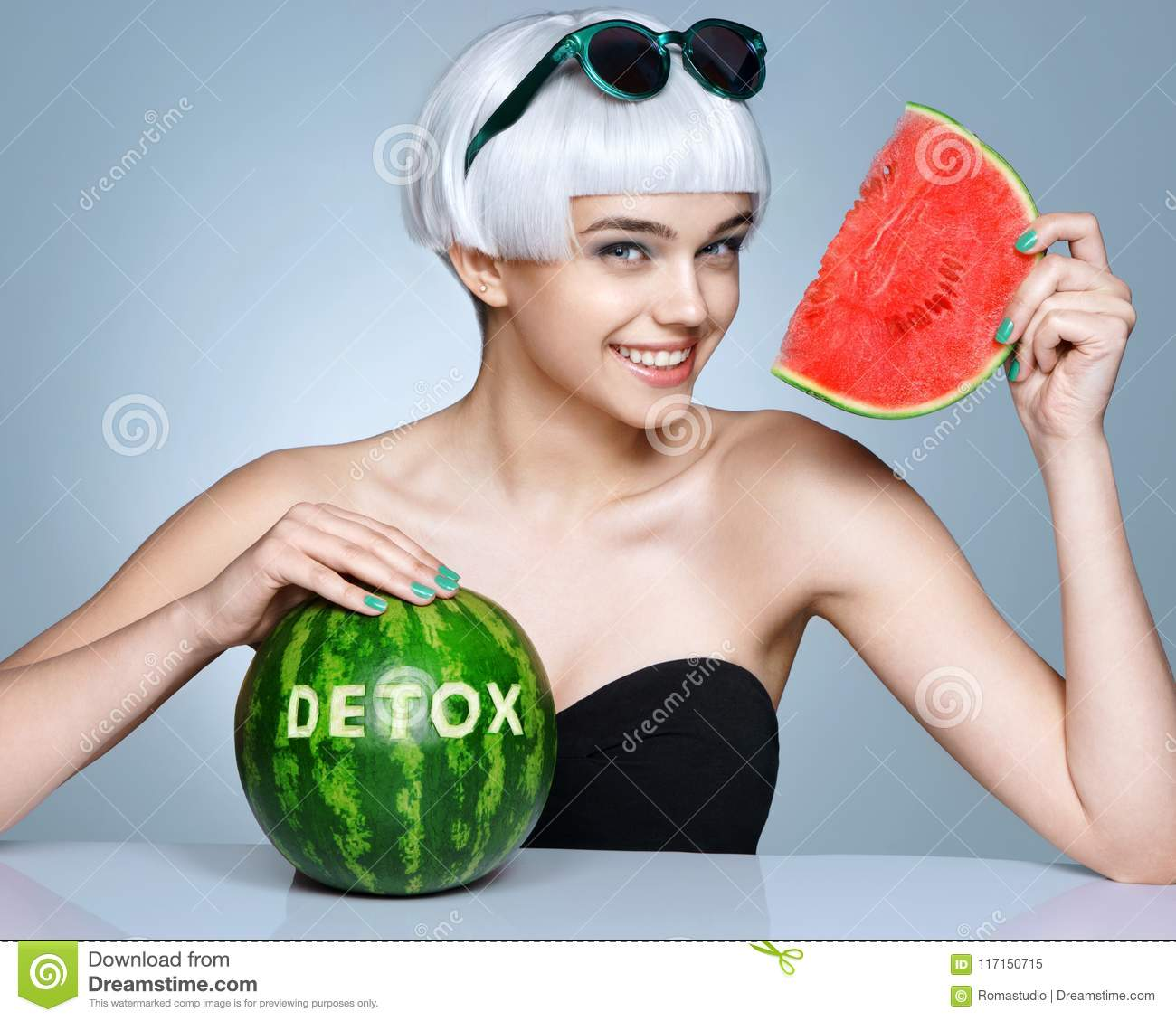 Happy girl with ripe watermelon on blue background.