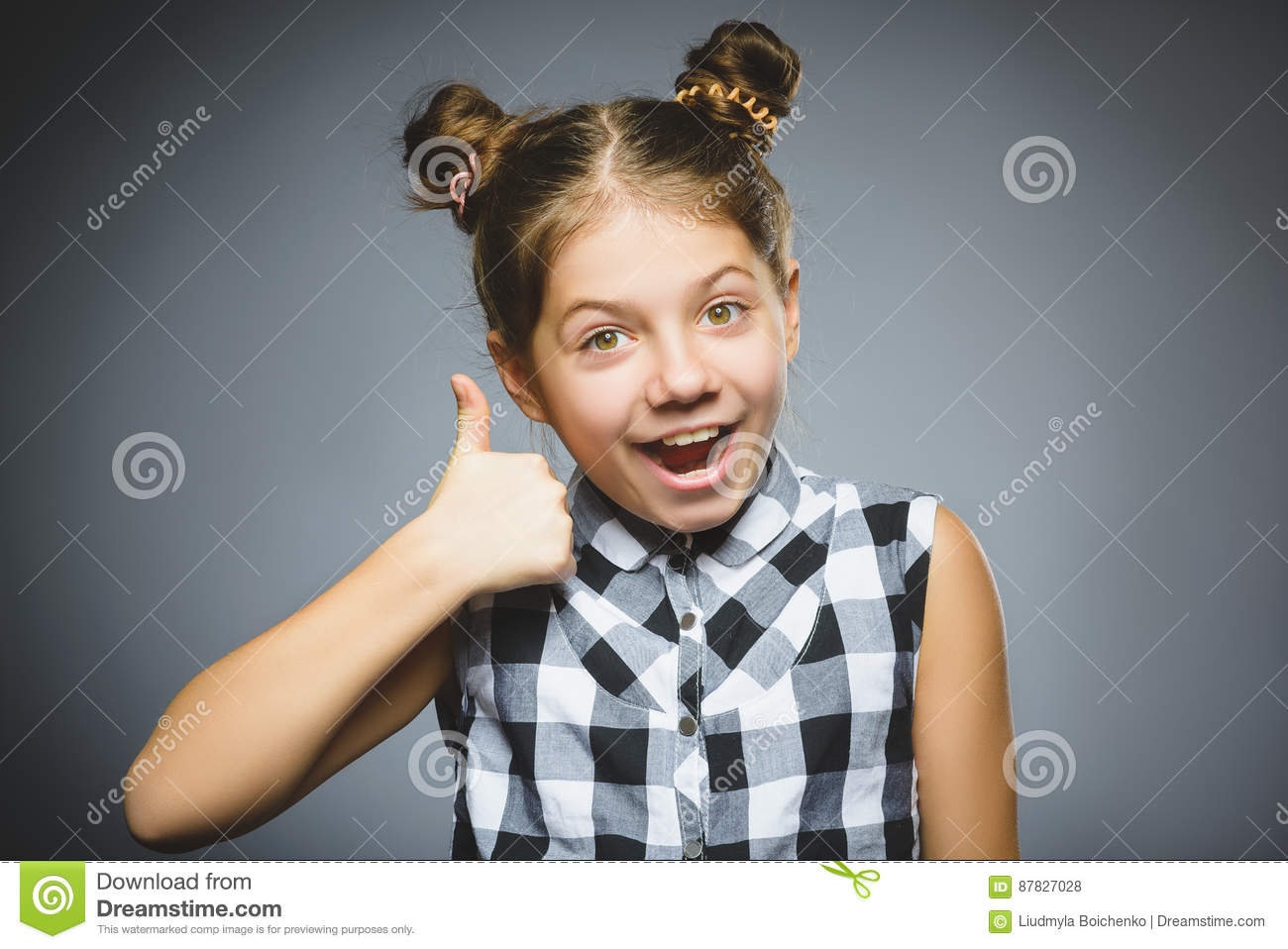 Happy girl showing thubs up. Closeup Portrait child smiling isolated on grey