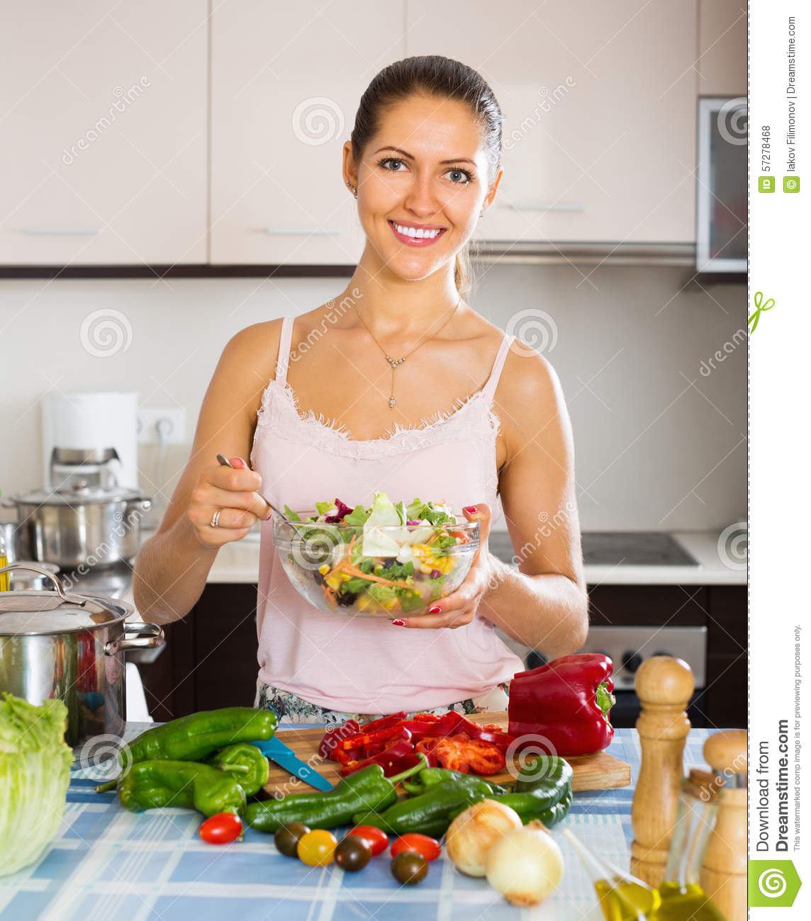 Happy Girl Standing At Kitchen Table Stock Photo