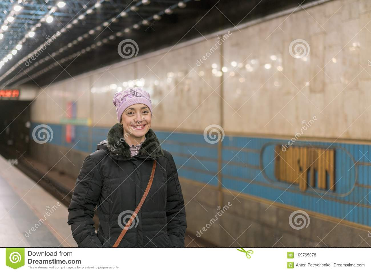 Happy girl standing on the platform of the subway