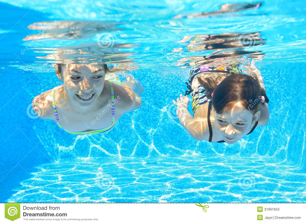 Kids Swimming Underwater two children swimming underwater pool stock photos, images