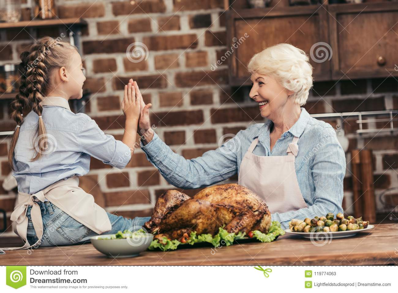 happy grandmother and granddaughter giving high five on thanksgiving after successful