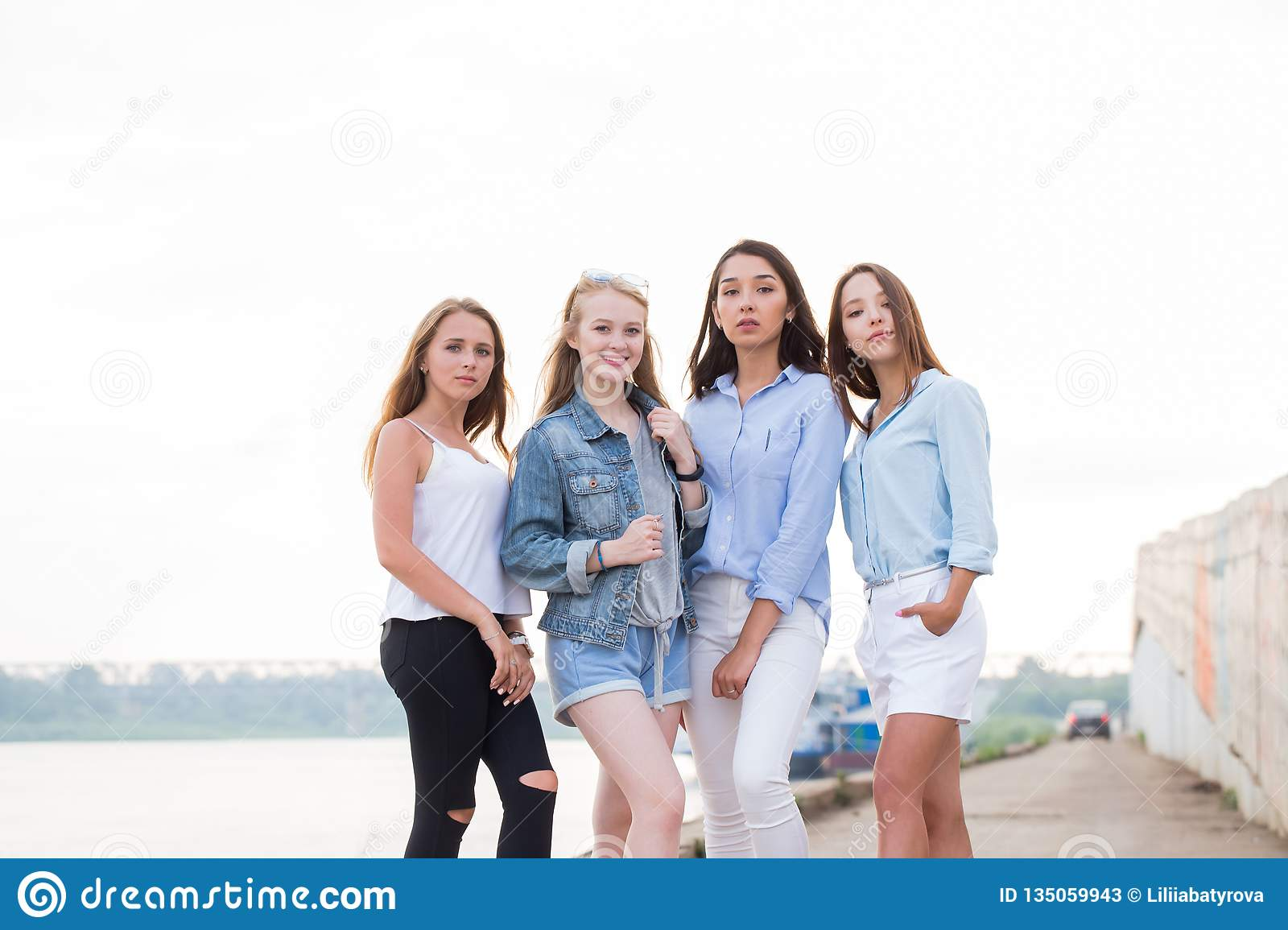 Happy group of female friends looking at camera and smile. Young girl student after College