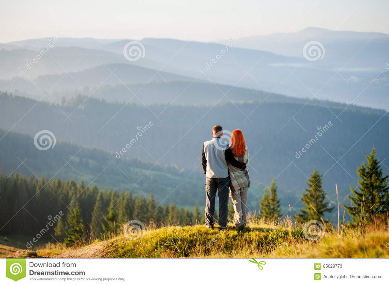 Happy guy and girl in the mountains in the morning
