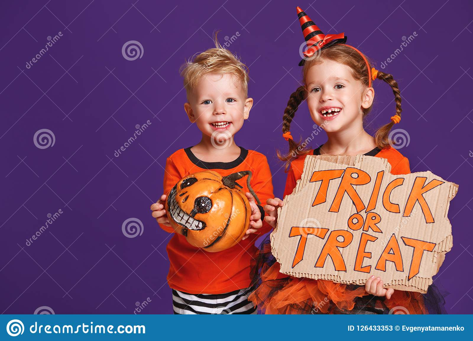 Happy Halloween! cheerful children in costume with pumpkins on v