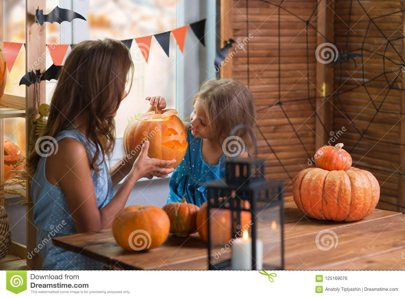 Happy Halloween. Family little beautiful girl with mother celebrating home with pumpkins