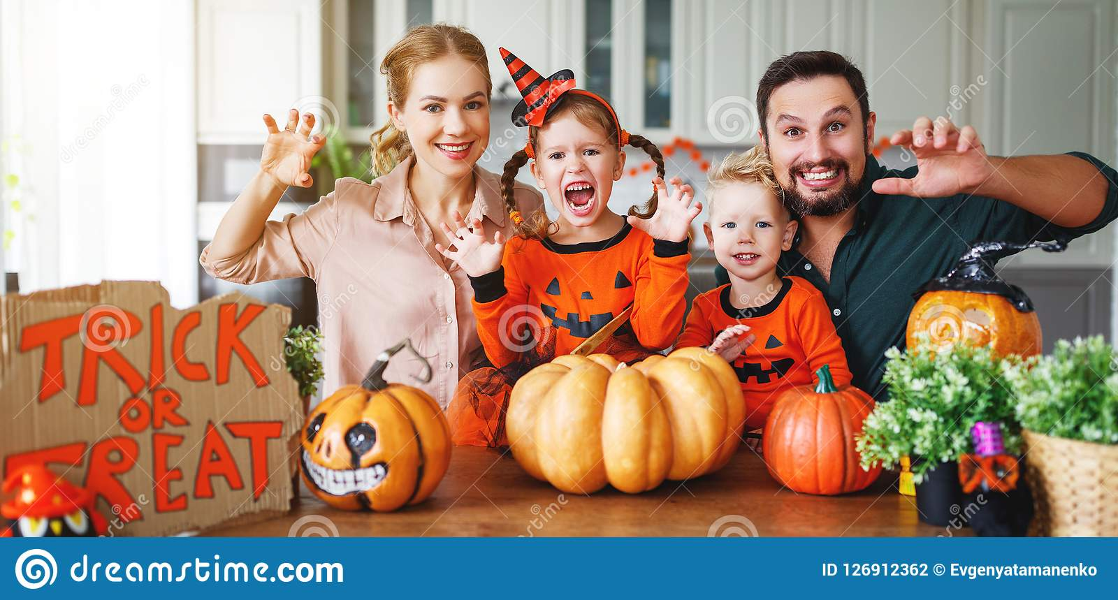 Happy Halloween! family mother father and children cut pumpkin f