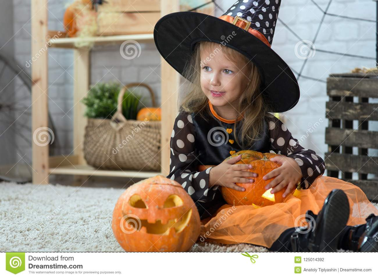 Happy Halloween. A little beautiful girl in a witch costume celebrates a home in an interior
