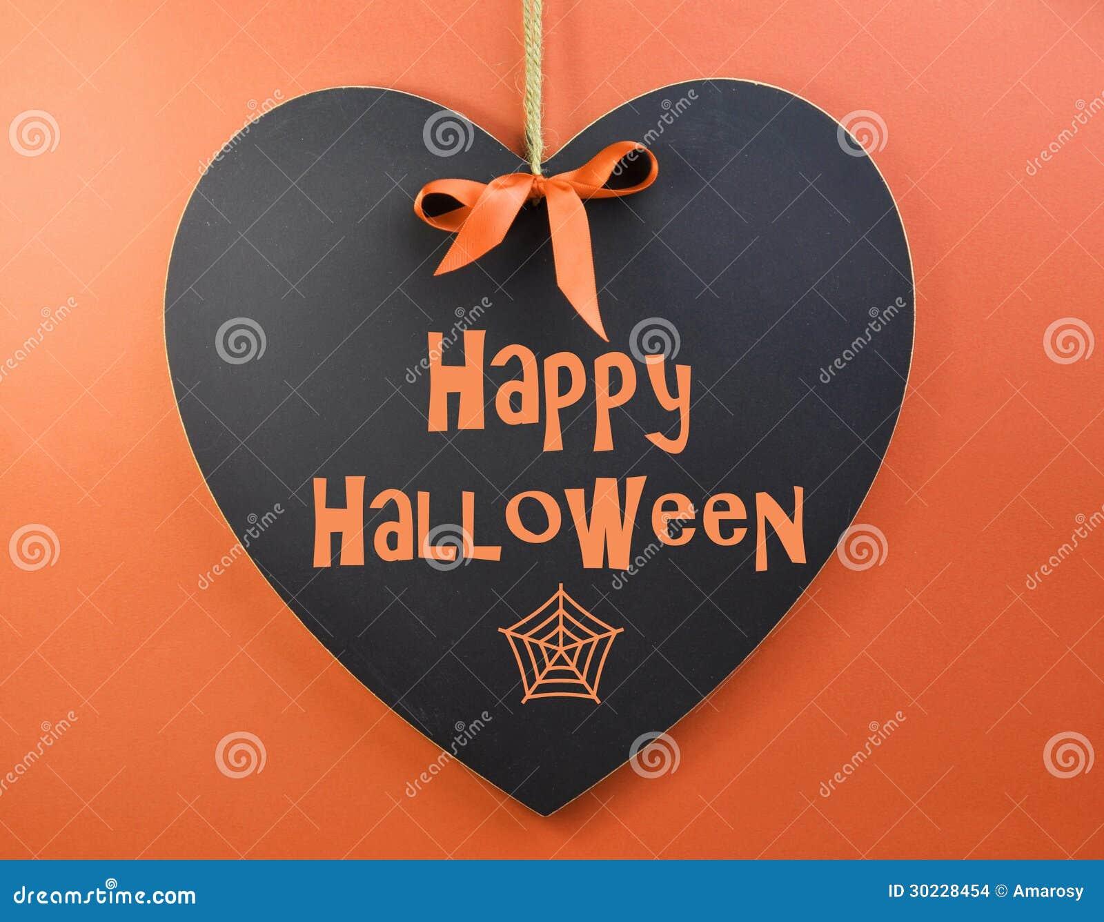 happy halloween message written on heart shape blackboard stock
