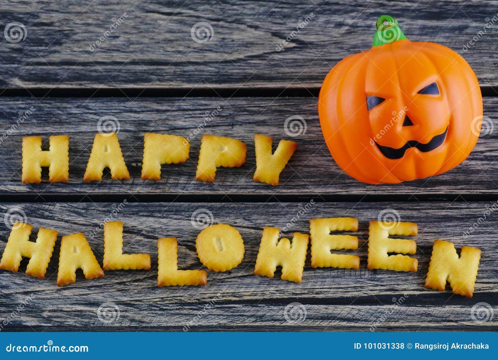 Happy Halloween words decoration with jack lantern pumpkin on wooden background