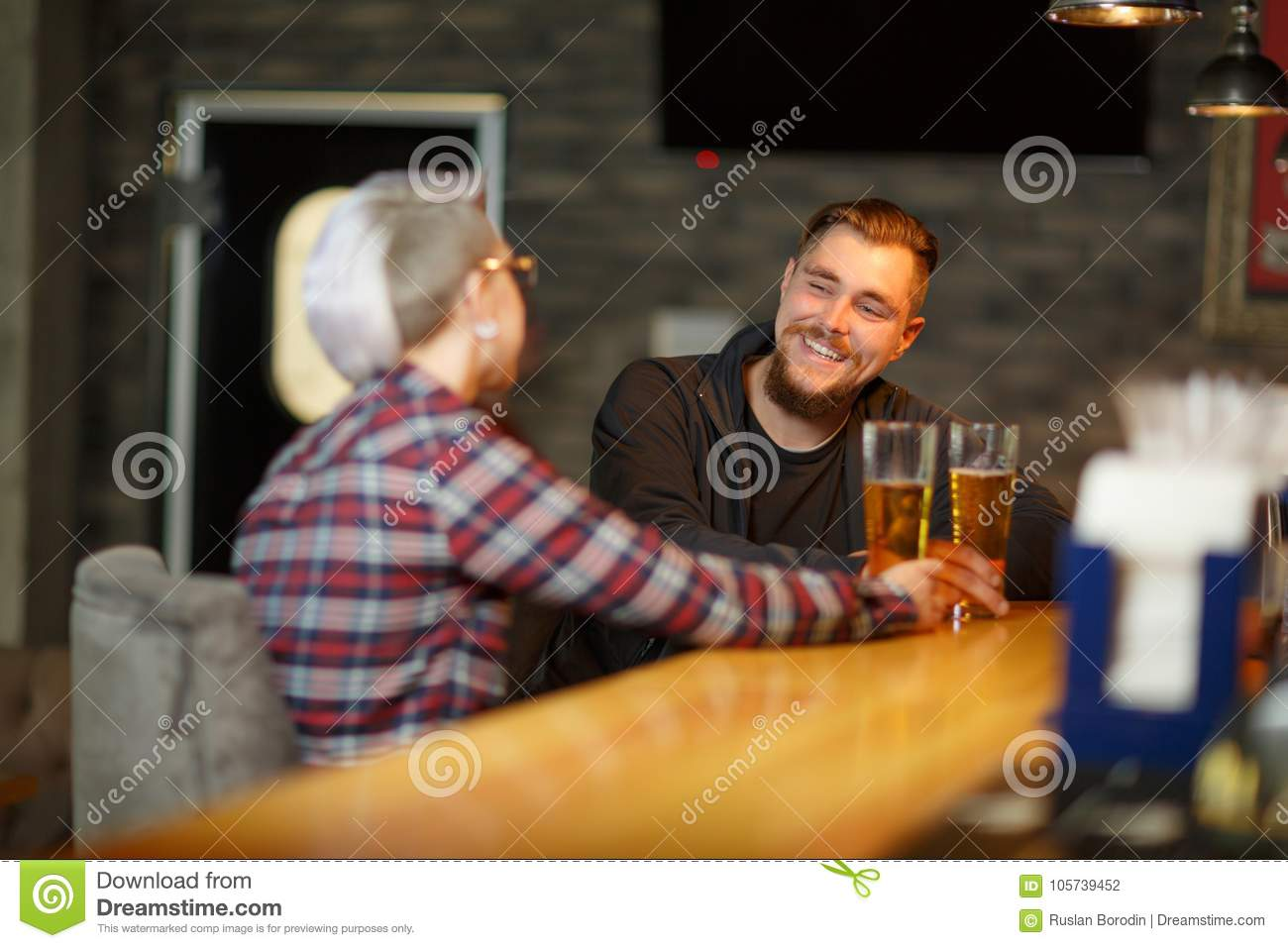 A happy guy, sitting and talking in a bar with a girl, drinking beer and laughing. Indoors.