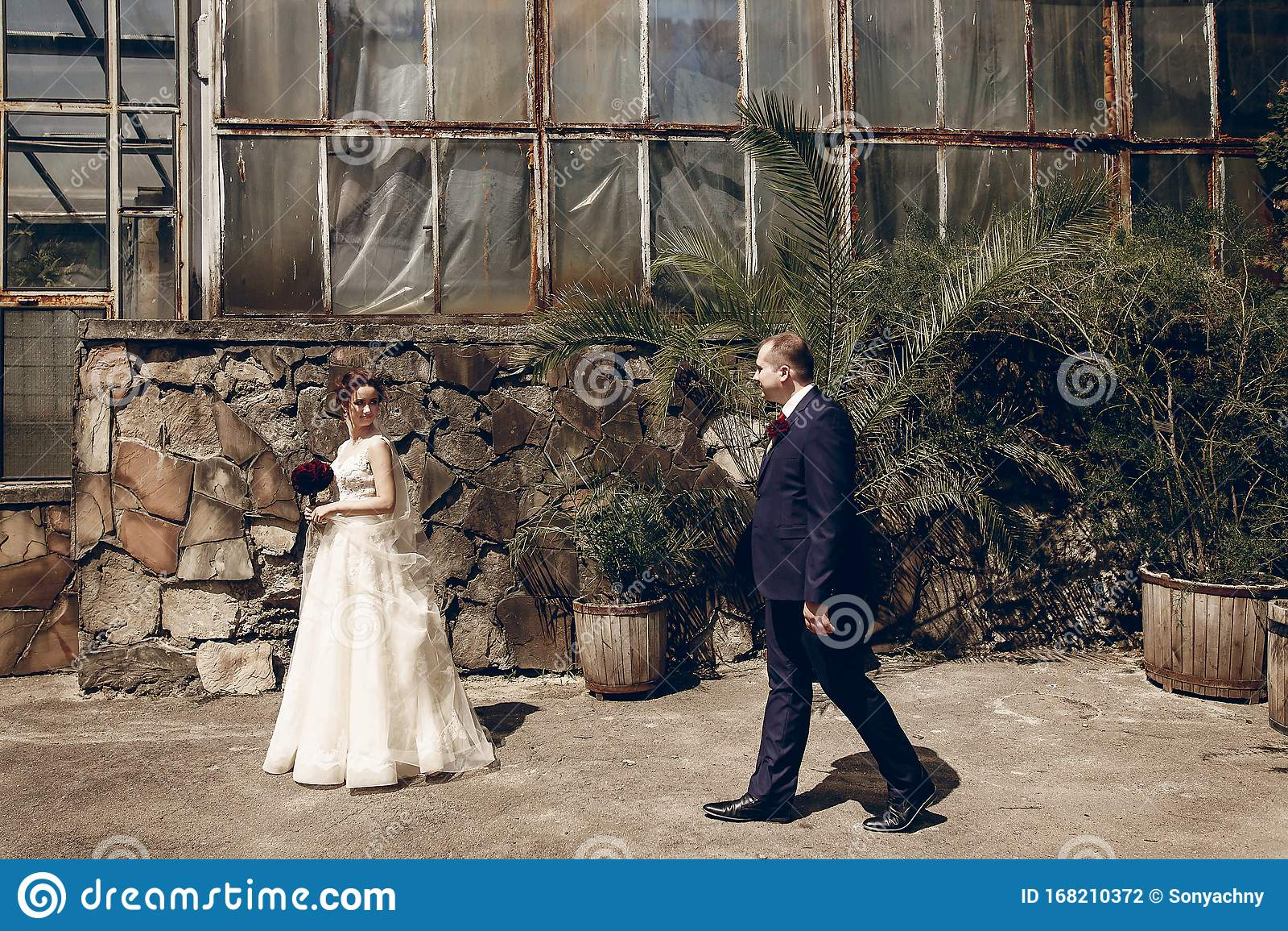 Happy Handsome Groom Walking With Beautiful Brunette Bride In