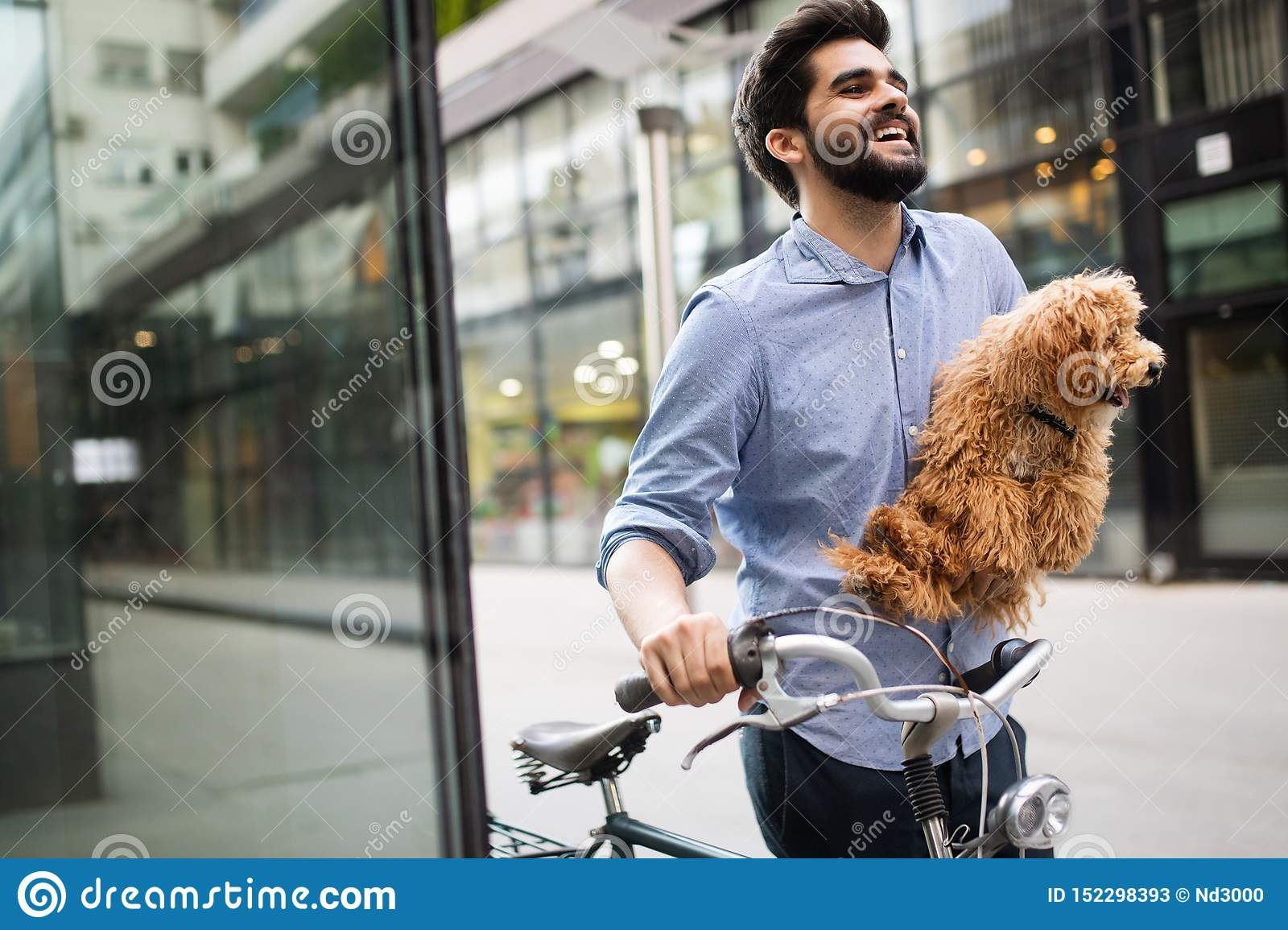 Happy young man holding dog in hands outdoors in city