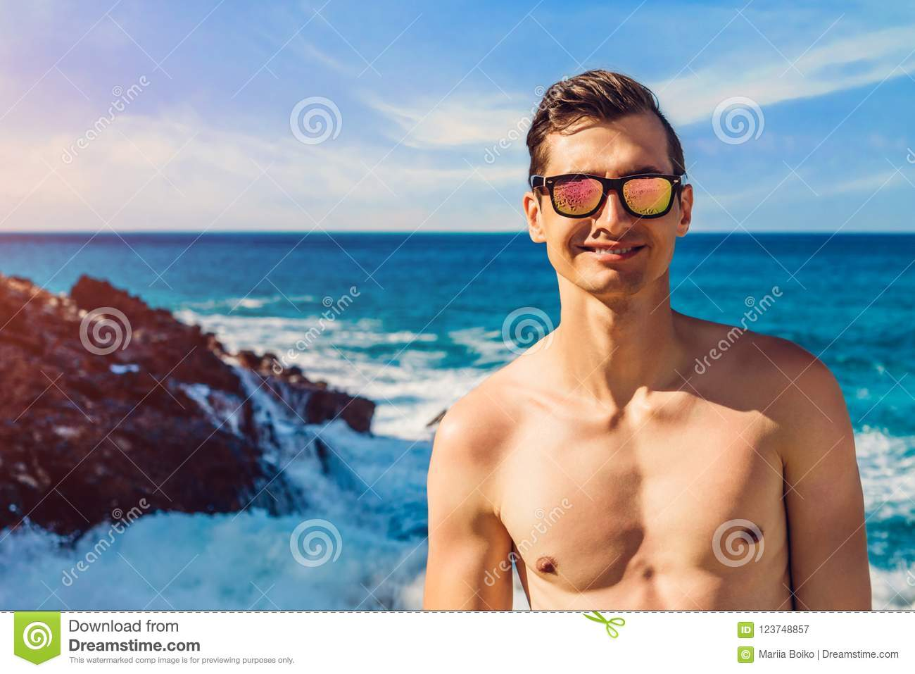 704e23b23a Happy handsome man walks on the beach by sea coast. Topless guy wearing  sunglasses. Summer vacation