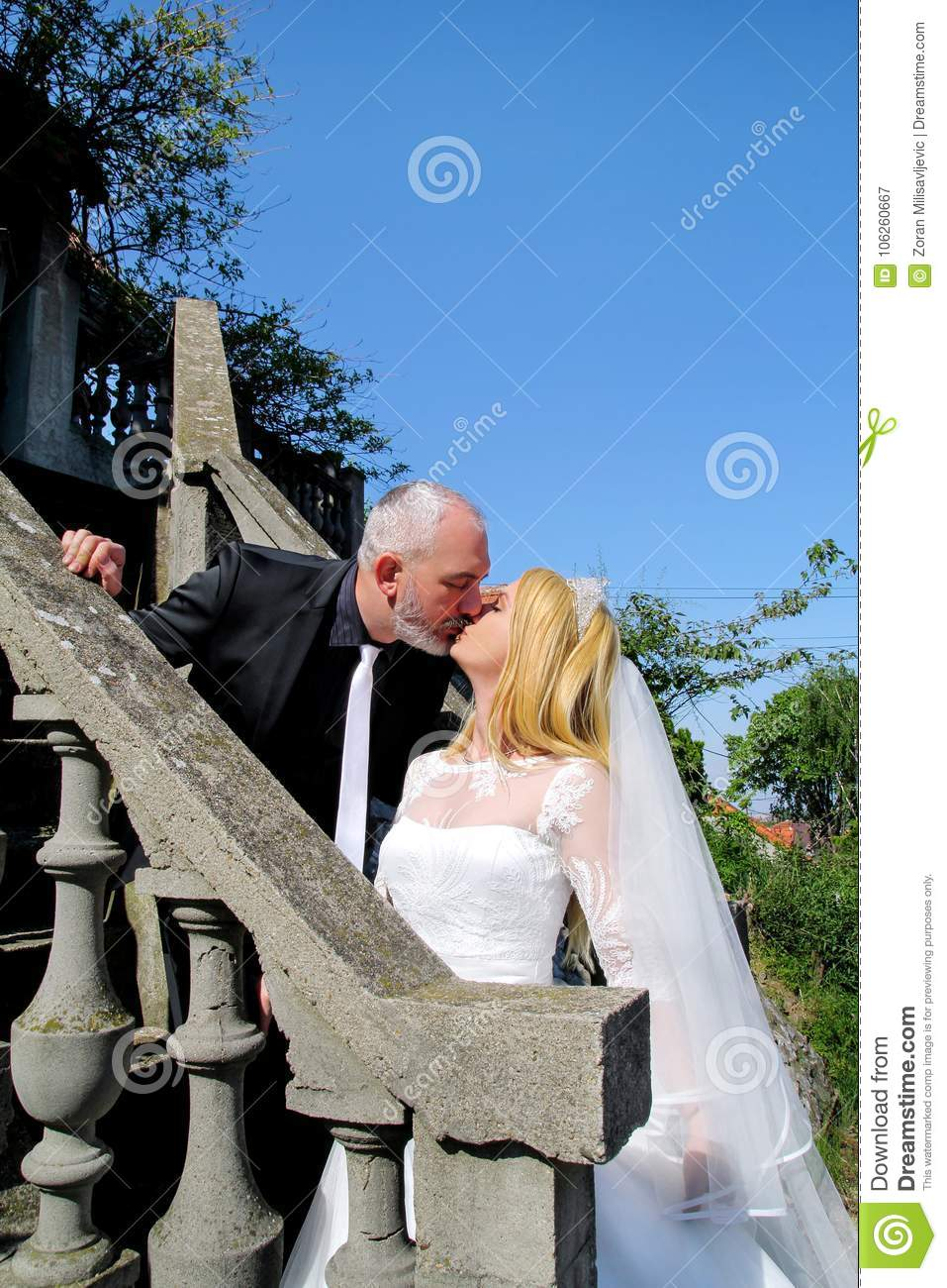 The happy handsome wedding couple are standing and kissing on stone steps in front of house.