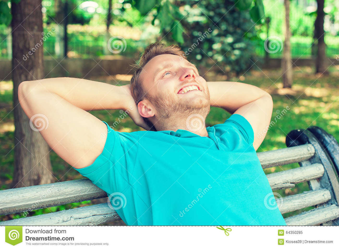 Happy handsome young man in shirt looking upwards in thought, relaxing on a bench