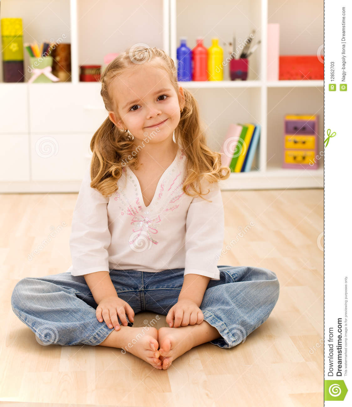 Happy healthy little girl sitting on the floor stock image for On the floor