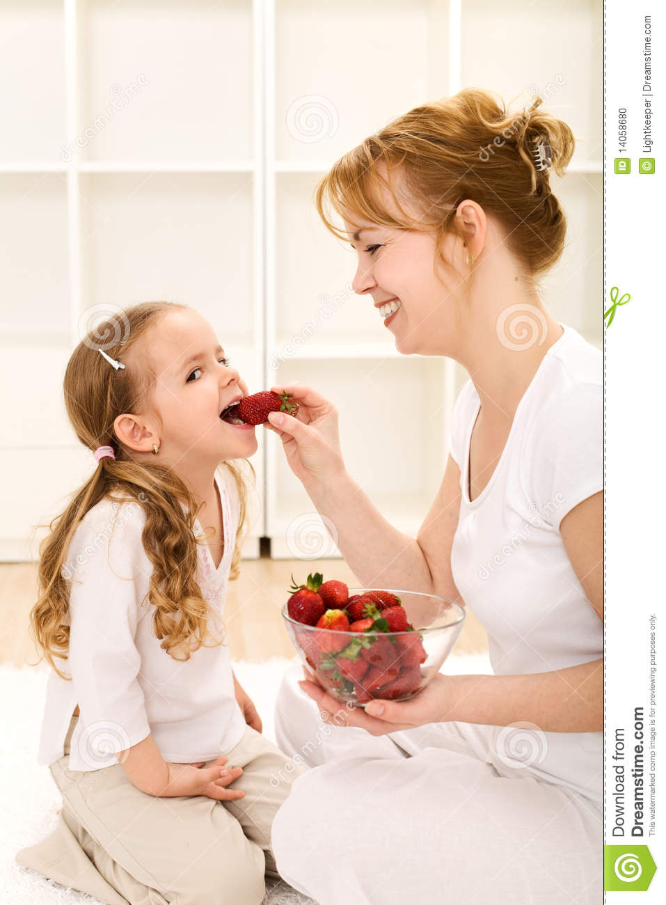 Happy healthy little girl and her mother eating fresh strawberries