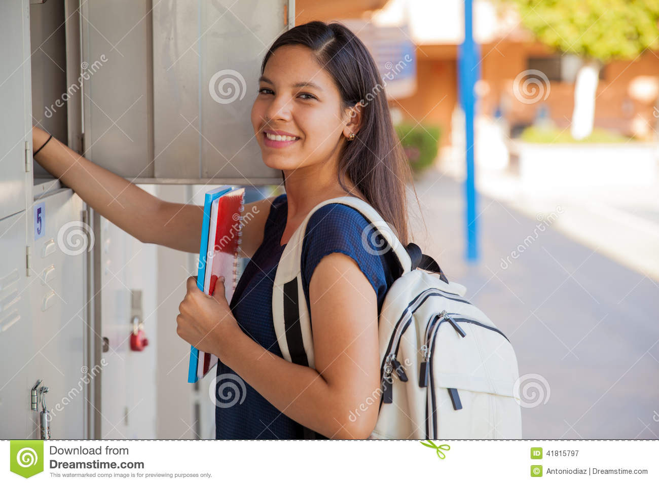 2c84719d3 Cute Hispanic girl carrying some books and a backpack in high school