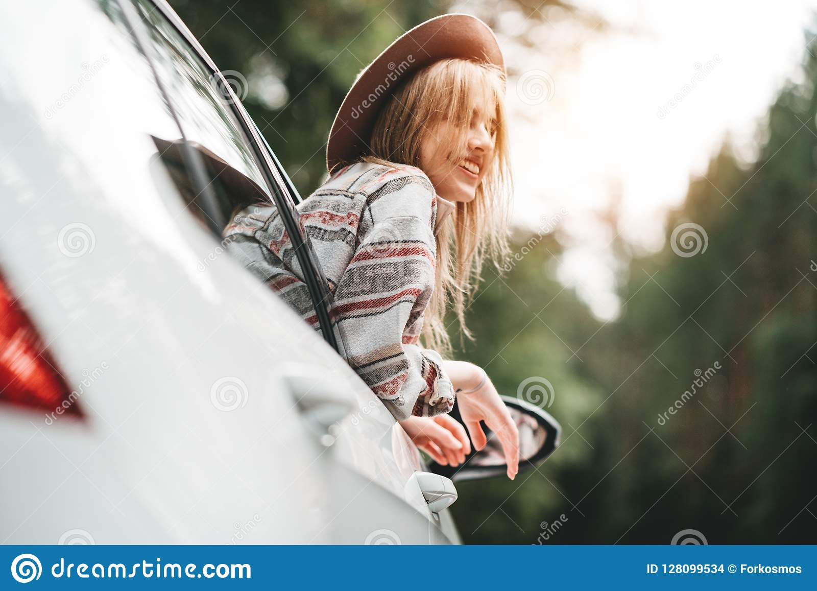 Happy hipster girl traveling adventure vacations. Boho woman sitting in car looking from window on view in country road