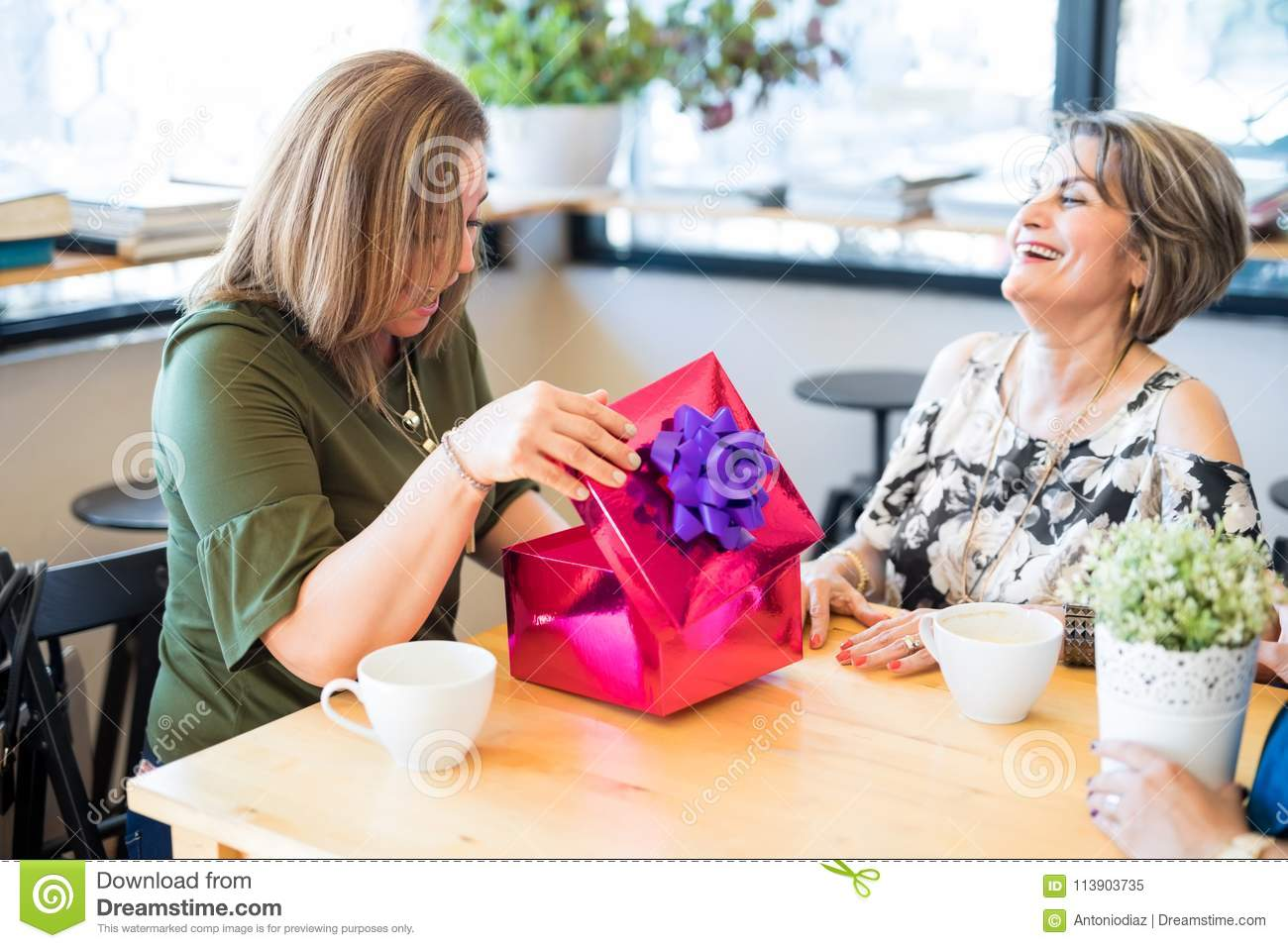 Happy Hispanic Women Feeling Surprised With Gift From Best Friends In A Restaurant